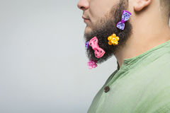 Man portrait with hair clips on the beard. Man portrait n profile with hair clips on the beard over gray background Royalty Free Stock Image