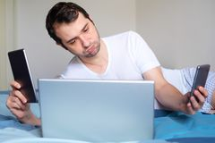 Man portrait lying in bed with internet technology devices. Concept of multitasking and internet tech addiction.Man surrounded by smartphone and digital devices Stock Image