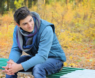 Man portrait sitting in autumn park on a bench. Stock Photo