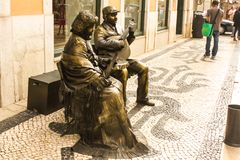 Street entertainers in Lisboa, Portugal. Man with Portuguese guitar and woman in traditional dress playing statues representing fado, traditional Portuguese Royalty Free Stock Photo
