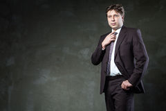 Man poses in his suit front of grunge wall Stock Photography