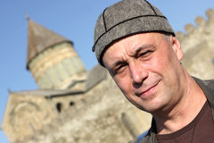 Man poses in national georgian hat. The man poses in national georgian hat on church background in Georgia Stock Photo