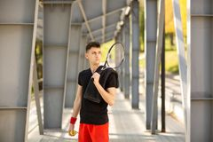 The man poses outdoors with a tennis racket and a ball. A towel is hanging on his shoulder. Sport concept.  stock photo