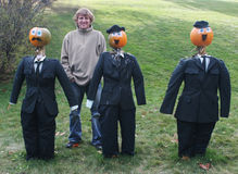 Man poses with pumpkin people in suits Royalty Free Stock Photo