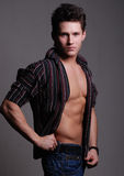 Man posing. Studio portrait of a serious, muscular young man in profile with his shirt unbuttoned Stock Photos