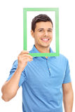 Man posing behind a green picture frame Stock Photo