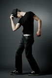 Man posing in black t-shirt and black hat. Stock Photo