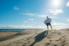 Man posing with board at Te Paki sand dunes Royalty Free Stock Photos