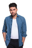 Man posing for the camera with his hands in pockets. Attractive young casual man posing for the camera with his hands in pockets, isolated on white background Stock Photos