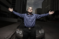 Man posing by a car at night Stock Image