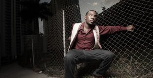Man posing on a chain link fence Stock Photography
