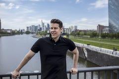 Man Posing on City Bridge and Frankfurt Skyline Behind. Man posing on a city bridge and Frankfurt`s skyline in the background Stock Image