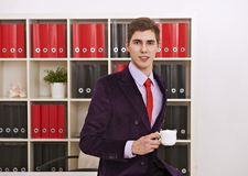 Man posing with coffee cup in office Royalty Free Stock Photos