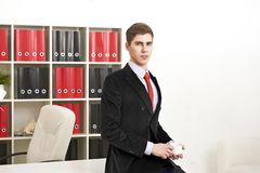 Man posing with coffee cup in office Stock Image