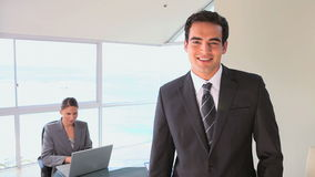 Man posing while a colleague is working behind. In a bright office stock video