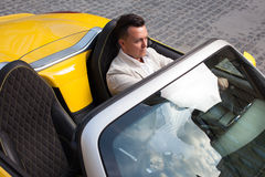 Man posing with convertible sportcar Royalty Free Stock Image