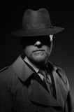 Noir movie character. Man posing in the dark with a fedora hat and a trench coat, 1950s noir film style character stock photos