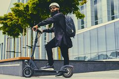 A man posing on electric scooter. Stylish bearded male in sunglasses posing on electric scooter in over modern building background Royalty Free Stock Photography