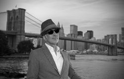 Man posing in front of Brooklyn Bridge. Wearing a hat Stock Photo