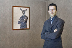 Man posing by a funny painting Stock Photography