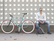 Man posing with his fixed gear bicycle. Wearing a hat and sunglasses Royalty Free Stock Image