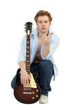 Man posing with his guitar. Young man posing with his guitar and giving the thumb's up Royalty Free Stock Photos