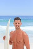 Man posing with his surfboard. Young man posing with his surfboard Royalty Free Stock Photography
