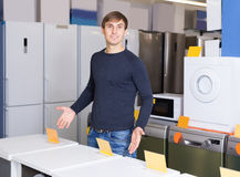 Man posing at household appliances section of supermarket Stock Photo