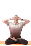 Man posing in lotus position, his eyes closed Stock Images