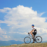 A man posing with a mountain bike on a ridge Stock Photo