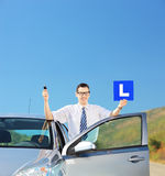 Man posing near his car, holding L sign and key on an open road Stock Photography