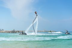 Man posing at new flyboard at Caribbean tropical beach. Positive human emotions, feelings, joy. Funny cute men making vacations an. D enjoying summer Stock Images