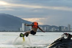 Man posing at new flyboard at tropical beach at sunset. Positive human emotions, feelings, joy. Funny cute men making vacations royalty free stock image