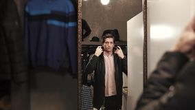 Man posing in a new jacket. Stylish young man is trying on a new winter jacket in shop. He is standing in front of a mirror and posing stock footage
