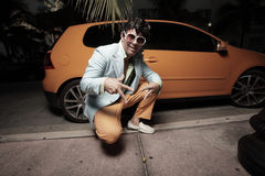 Man posing by an orange sports car Royalty Free Stock Photos