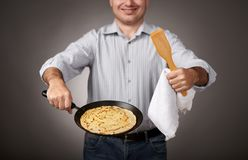 Man posing with a pancake in a pan, white shirt and pants, gray background, shallow depth of field, sharp pancake and blurred face royalty free stock photos