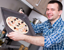 Man posing with pizza on baking sheet Royalty Free Stock Image