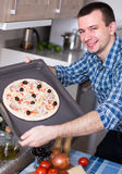 Man posing with pizza on baking sheet Royalty Free Stock Photos