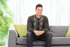 Man posing seated on a sofa at home Stock Image