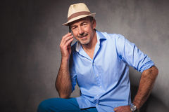 Man posing seated while talking on the phone Royalty Free Stock Photography