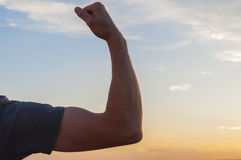 Man posing at sunset, sowing biceps. Nature background Stock Photo