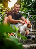 Man posing with ther dog after bycicle riding. Royalty Free Stock Photography