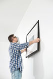 Man positioning picture frame on wall Stock Images