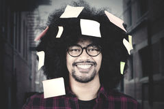 Man with post it on hair. Afro man wearing glasses and smiling at the camera with post it attached on his curly hair Stock Images