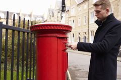 Man Posting Letter In Red British Postbox Royalty Free Stock Images
