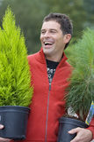 Man with potted plants, smiling Stock Photo