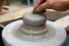 Man potter hands working on pottery clay wheel Stock Photos