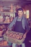 Man potter holding ceramic vessels in atelier Stock Photo