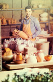 Man potter holding ceramic vessels in atelier Stock Images