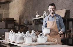 Man potter holding ceramic vessels in atelier. Positive man potter holding ceramic vessels in atelier royalty free stock images
